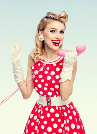 Foto luminosa di bella donna felice con il telefono, vestita in abito rosso stile pin-up a pois e guanti bianchi. Modello biondo caucasico che posa nel tiro dello studio retrò.
