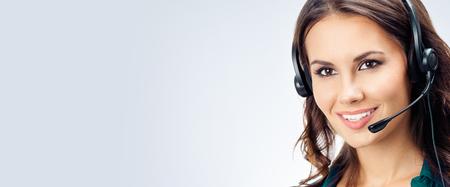 회색 배경에 헤드셋, 녹색 자신감 있는 옷을 입은 행복한 미소 짓는 아름다운 여성 전화 교환원의 초상화. 콜 센터 및 고객 지원 서비스 개념입니다.