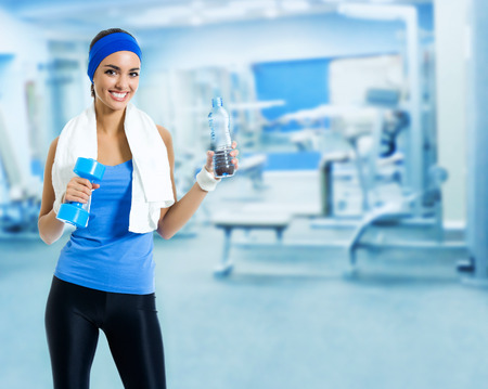 Portrait of happy smiling young woman in fitness wear with bottle of water, at sport club or center, with blank copyspace area for slogan or text Stock Photo