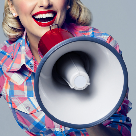 Closeup photo of happy woman with megaphone, dressed in pin-up style. Caucasian blond model posing in retro fashion and vintage concept image. Stock Photo