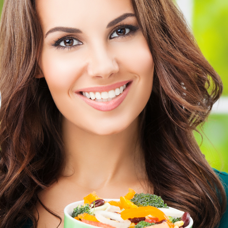 Portrait of smiling beautiful woman eating salad, outdoors, healthy eating and dieting concept photo