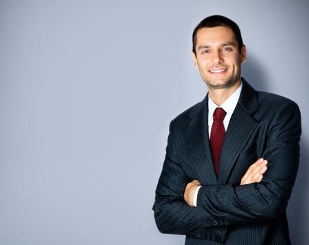 Foto bedrijfsconcept van lachende zelfverzekerde zakenman in zwart pak en rode stropdas, met gekruiste armen pose, lege kopie ruimte voor wat tekst, reclame of slogan, staande tegen een grijze achtergrond Stockfoto