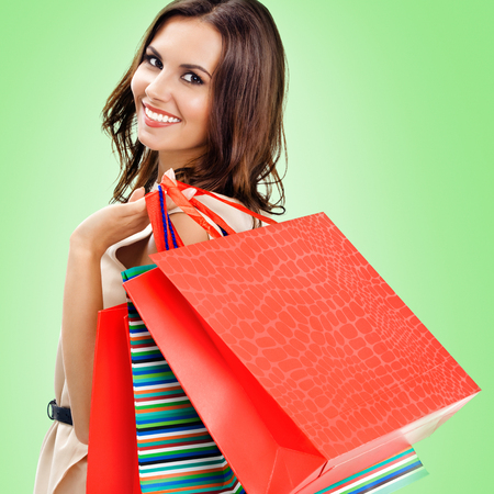 Bright color photo of young woman with red shopping bag, against green background, square composition image