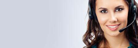 Foto van lachende vrolijke mooie vrouwelijke telefoonoperator in hoofdtelefoon, groene kleding, met lege kopie ruimte voor wat tekst, reclame of slogan, over grijze achtergrond. Callcenter en klantenservice dienstverleningsconcept. Stockfoto