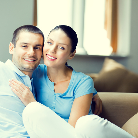 Portrait photo of young happy smiling attractive couple at home, square composition Imagens