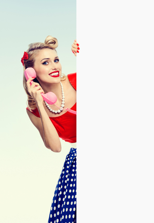 Bright photo of woman with phone, in pin-up style dress, showing blank signboard with copyspace area. Caucasian blond model posing in retro fashion and vintage concept studio shoot.