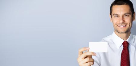 Foto del concetto di business dell'uomo d'affari che mostra una carta di credito aziendale o in plastica vuota, con spazio vuoto per la copia posto per un po' di testo, pubblicità o slogan, su sfondo grigio