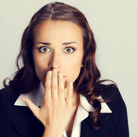 Portrait of surprised excited young business woman covering with hands her mouth