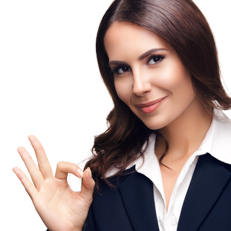 Photo of happy smiling beautiful young businesswoman showing okay gesture, isolated against white background