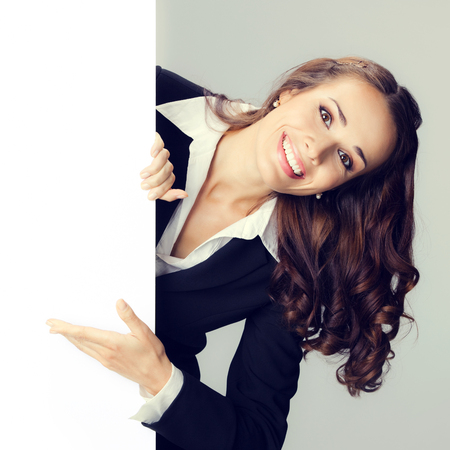 Portrait of happy smiling woman in black confident suit showing blank signboard with copyspace empty area for some text or slogan, over grey background. Business and advertising concept photo. Stock Photo