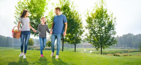 ピクニック幸せな家族、田舎や公園に行く写真。幸せな子供時代と夏のコンセプトイメージ。いくつかのテキスト、広告やスローガンのための空白の場所をコピーします。晴れた日の写真。