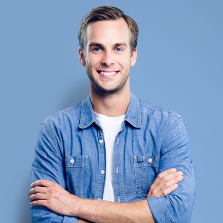 Man portrait. Young happy man with smiling face. Male model in crossed arms pose. Blue background. Guy in casual fashion clothing, studio photo. Square composition picture.
