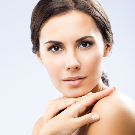 portrait of beautiful young woman with shoulders, on grey background 版權商用圖片