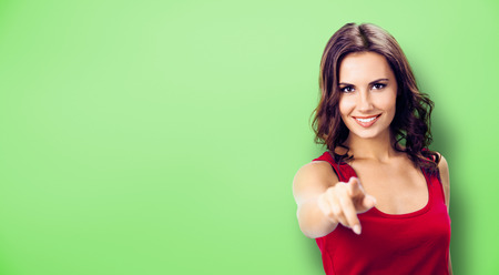 Pointing at You - advertising concept photo. Smiling woman in red, showing copy space, visual imaginary or something, or pressing virtual button, green background. Copyspace for some text or slogan.