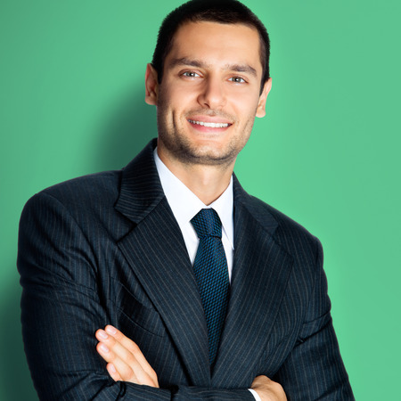 Portrait photo of happy confident businessman in black suit and blue tie, with crossed arms pose, standing against green color wall background. Success in business concept picture.