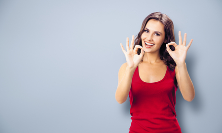 Portrait photo - young happy smiling beautiful woman in casual clothing, showing okay gesture, or zero hand sign, over grey color wall background. Girl in red dress. Brunette excited model at studio.