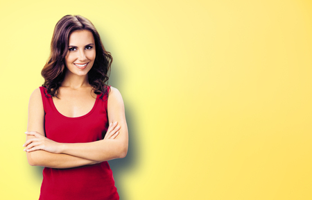 Portrait photo - young smiling woman in casual red clothing, in crossed arms pose. Yellow background. Happy beautiful girl at studio. Brunette Model with long hair posing at studio picture.