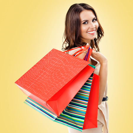 Shopping woman. Happy girl holding grocery bags, over yellow color background. Copyspace for some slogan, advertising or text. Square composition. Consumerism, sales and shopaholic concept picture.