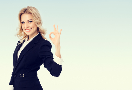 Photo of happy smiling beautiful young businesswoman showing okay gesture, with blank copyspace area for text or slogan