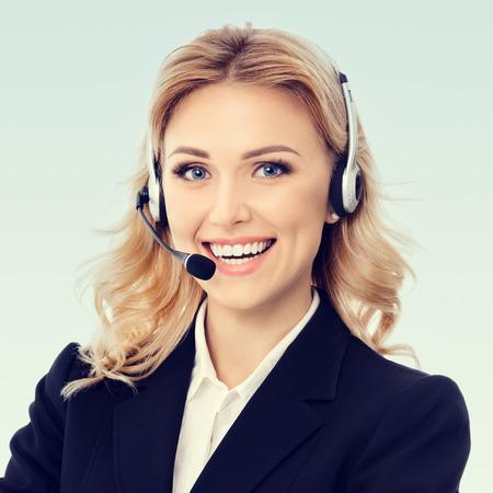 Servicio de Call Center. Foto del agente de atención al cliente. Operadora de telefonía llamada o recepcionista femenina Línea de ayuda contestadora y telemarketing. Chica rubia caucásica en chaqueta negra de confianza, en el estudio de imagen. Composición cuadrada. Foto de archivo