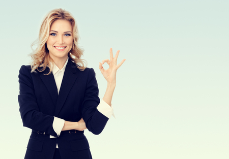 Photo of happy smiling beautiful young businesswoman showing okay gesture, with blank copy space area for some text or slogan