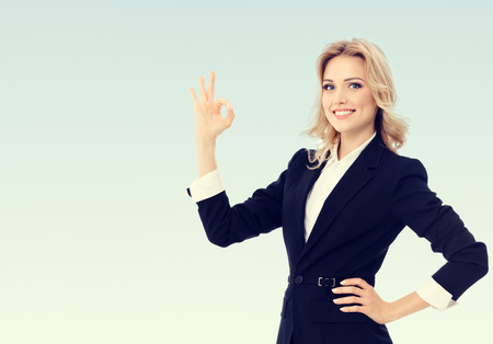 Photo of happy smiling beautiful young businesswoman showing okay gesture, with blank copy space area for some adverising text or slogan