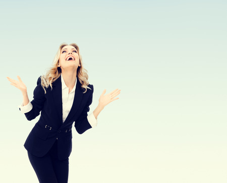 Photo of happy gesturing young cheerful businesswoman, with blank copyspace area for text or slogan