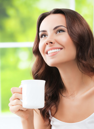 Portrait of young happy girl drinking coffee or tea, at home
