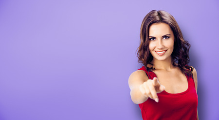 Photo of smiling young woman in red clothing, showing copyspace, visual imaginary or something, or pressing virtual button, violet background. Pointing at You - advertising concept picture.