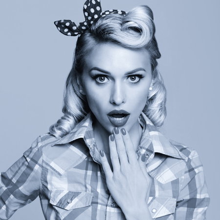 Portrait photo of beautiful young surprised woman, dressed in pin-up style. Caucasian blond girl posing in retro fashion and vintage concept. Black and white. Square composition image.