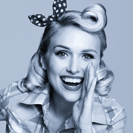 Portrait of beautiful young happy smiling woman, dressed in pin-up style. Caucasian blond model posing in retro fashion and vintage concept. Black and white. Square composition picture.