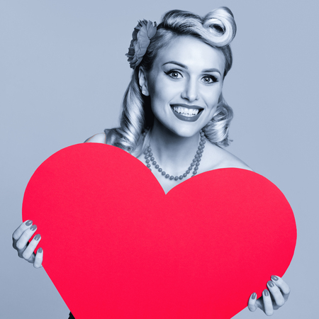 Portrait photo of beautiful young happy smiling woman holding red heart symbol, dressed in pin-up style. Caucasian blond girl posing in retro fashion and vintage concept. Black and white image. Square composition.