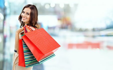 Shopping woman. Happy girl holding grocery bags, at mall background. Copyspace for some slogan, advertising or text. Brunette model - consumerism, sales and shopaholic concept picture.