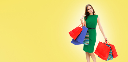 Shopping woman. Happy excited girl in green dress, holding bags, yellow color background. Copy space for some slogan, advertising or text. Consumerism, sales and shopaholic concept. Banner composition.