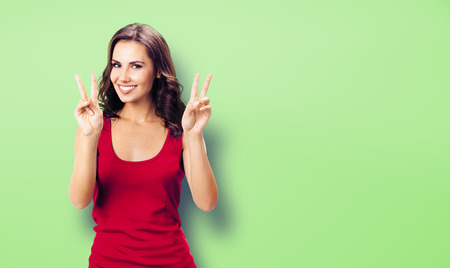 Portrait photo - young happy smiling woman in casual clothing, showing two fingers or victory gesture, over green color background. Happy girl in red dress. Brunette excited model at studio picture.