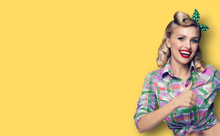 Pin up girl. Excited happy woman showing thumb up gesture or like sign. Retro fashion and vintage concept. Yellow color background. Copy space for some advertise slogan, imaginary or text.