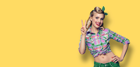 Pin up girl. Excited happy woman showing two fingers or victory gesture hand sign. Retro fashion and vintage concept. Yellow color background. Copy space for some advertise slogan, imaginary or text.