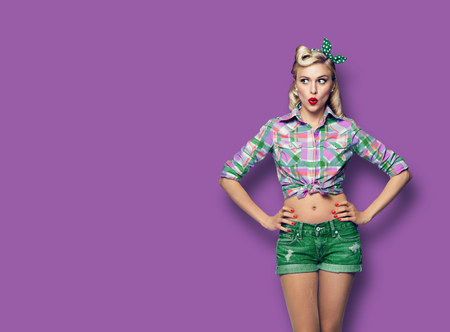 Excited surprised woman. Girl in pin up style, looking sideways. Blond model at retro fashion and vintage concept. Violet purpure color background. Copy space for some advertise slogan, sign or text. Фото со стока