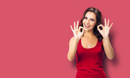 Portrait photo - young happy smiling beautiful woman in casual clothing, showing okay gesture, or zero hand sign, red color wall background. Brunette excited girl at studio.