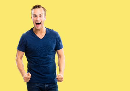 Yes, I did it! Very happy young man, isolated over yellow color background. Emotions and success concept. Excited male model with open mouth, in blue smart casual wear at studio picture. Copy space.