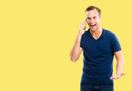 Good news! Very happy excited young man in blue casual clothing talking on smart phone, isolated over yellow color background. Mobile, cell, emotions and success concept. Copy space for some text.