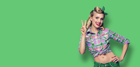 Pin up girl. Excited happy woman showing two fingers or victory gesture hand sign. Retro and vintage concept. Green color background. Copy space for some advertise slogan, sign or text.