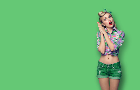 Excited surprised beauty woman. Girl in pin up fashion style. Blond model at retro and vintage concept. Green color background. Copy space for some advertise slogan, imaginary or text.