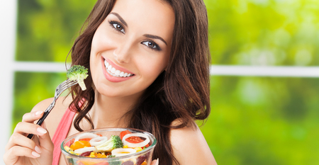 Portrait photo of young happy smiling woman with salad, outdoors, with copyspace
