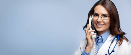 Portrait picture of happy smiling young doctor with phone, on grey background. Copy space for some sign, slogan or advertising text.