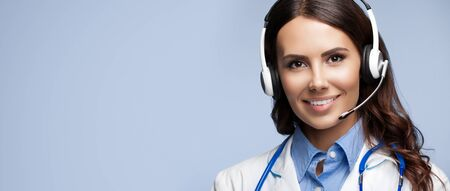 Medical call center servise. Portrait of happy smiling doctor in headset, on grey background, with copy space empty place for sign text.