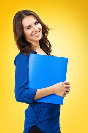 Portrait of young happy smiling business woman with blue folder with copy space, isolated over yellow orange background. Brunette dark heared model at studio.