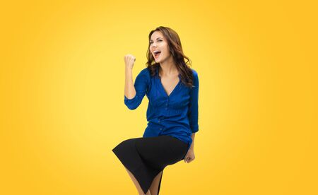Yes, I done it! Very happy gesturing young business woman. Excited girl with open mouth in blue confident clothing, isolated over yellow orange background. Brunette model at studio picture. Stock fotó