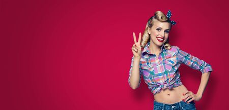 Pin up girl. Excited happy woman showing two fingers or victory gesture hand sign. Retro and vintage concept. Dark red color background. Copy space for some advertise slogan, sign or text.
