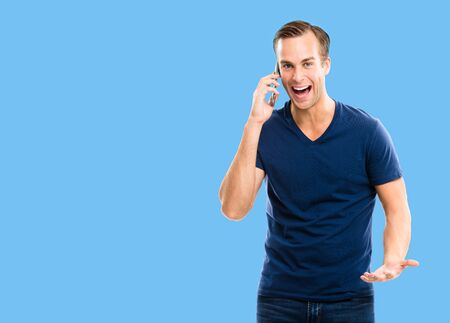 Good news! Very happy excited young man in blue casual clothing talking on smart phone, isolated over blue color background. Mobile, cell, emotions and success concept. Copy space for some text.